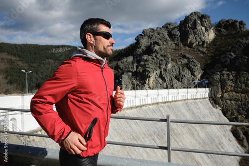 Plakat Sporty mężczyzna bieg i ćwiczy na halnej drodze w późnej zimie. Zdrowy trening na świeżym powietrzu.