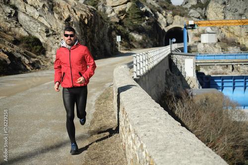 Plakat Sportowiec działa na górskiej drodze. Zdrowy trening na świeżym powietrzu pod koniec zimy.