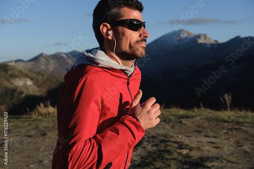 Plakat Mężczyzna biegać plenerowy w górze. Mężczyzna sportowiec szkolenia cross country pod koniec zimy.