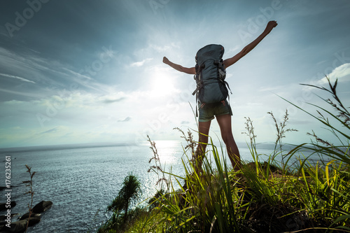 Tourist with backpack standing on sea coast with raised hands - Buy ... 0237a4561d2b7