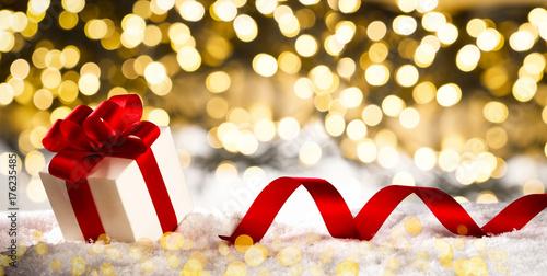 christmas gift banner red bow ribbon on snow light bokeh background
