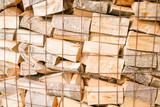 Close up of logs in a metal grid cage with a chopping block on a lumber yard