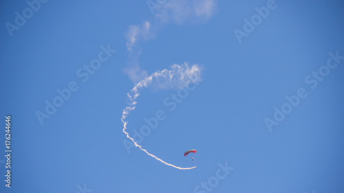 Poster Luchtsport Skydiver and colorful parachute on the blue sky background