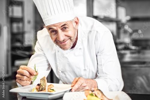 Fototapeta Smiling male chef garnishing food in kitchen