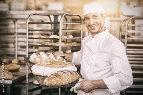 Stampa su Tela Smiling baker holding tray of bread