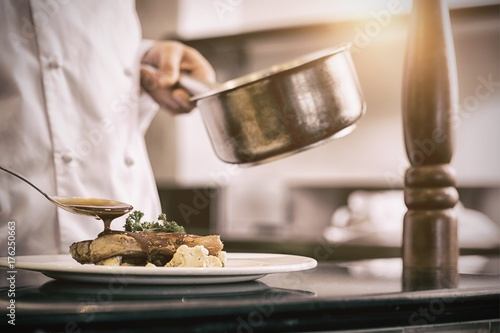 Closeup mid section of a chef garnishing food