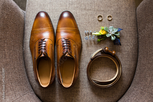Closeup of elegant stylish brown male accessories isolated on brown textile background of armchair. Top view of leather belt, pair of classic shoes, floral corsage, and two golden wedding rings.