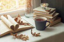 Autumn Still Life. Books, Leaves, Cup And Dry Tiny Flowers In Vase Red Candlestick On Window. Concept Of Autumn Reading Time And Romantic, Warm, Cozy Seat  Opened Book, Rustic Style Home Decor