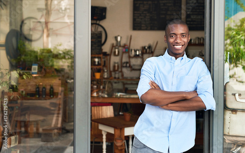 Fotografía  Smiling African entrepreneur standing at the door of his cafe