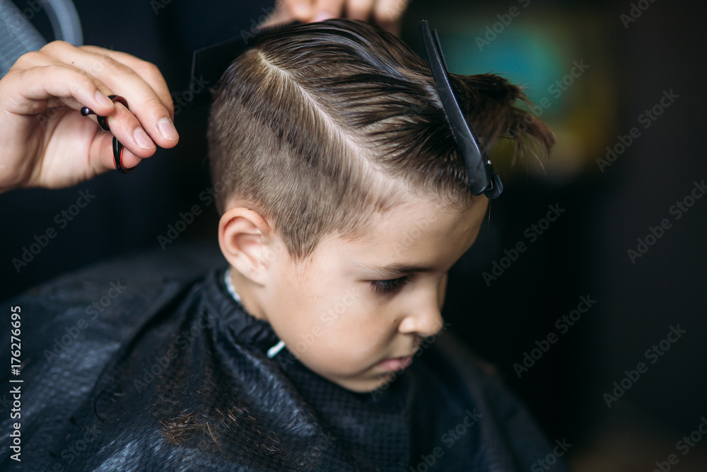 Fototapeta Little Boy Getting Haircut By Barber While Sitting In Chair At Barbershop.