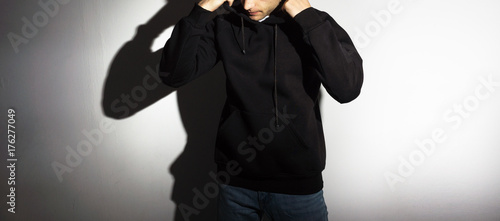 Fototapety, obrazy: the guy in the Blank black hoodie, sweatshirt, stand, smiling on a white background, mock up, free space, logo, template for print,  design