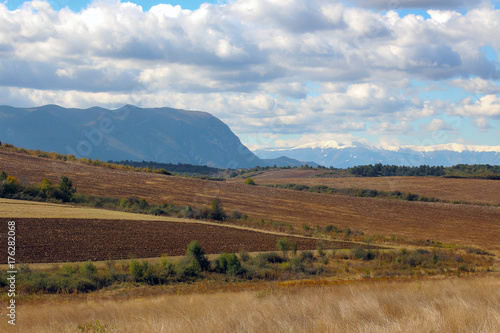Spoed Foto op Canvas Natuur Autumn landscape. Fields, mountains and white clouds in the blue sky.