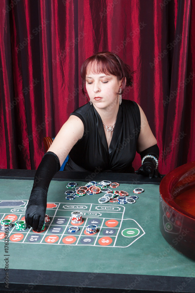 Plakat  young woman wearing  black gloves and black dress parlays in a casino