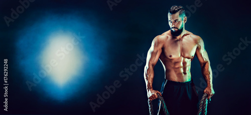 Fotografie, Obraz  Muscular bearded bodybuilder man Posing with ropein studio.