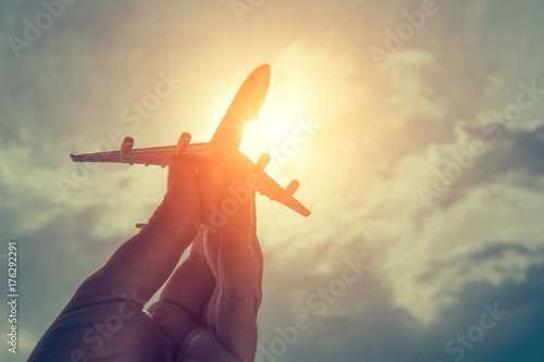 Türaufkleber Flugzeug hand holding airplane model in front of cloudy sky background. air transportation concept.