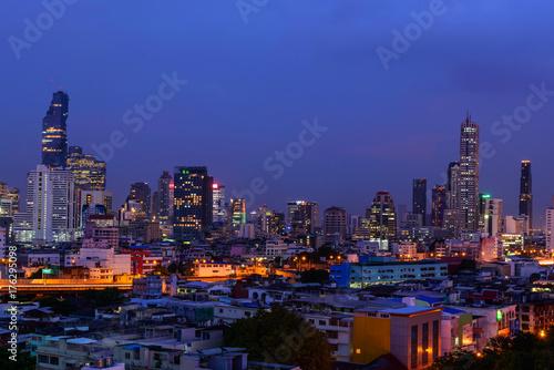 Plakat wysoki budynek miasta w porze nocnej