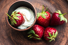 Fresh Strawberry With Whipping Cream On A Dark Plate
