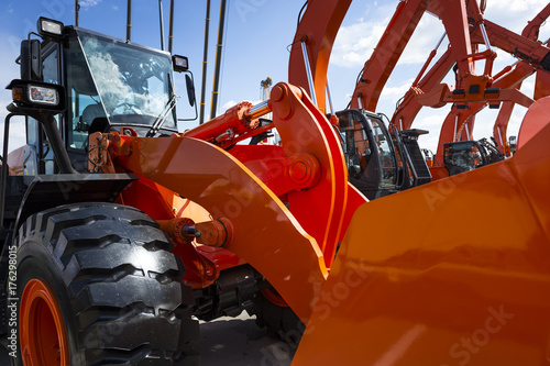 Fotografie, Obraz  Bulldozer with hydraulic piston of scoop and black wheels, other construction ma