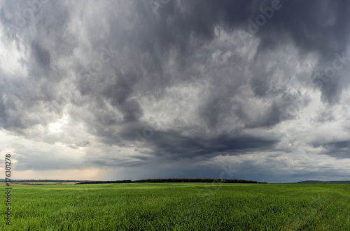 Poster Taupe Dramatic storm scene with rain at the horizon and rural path going towards left