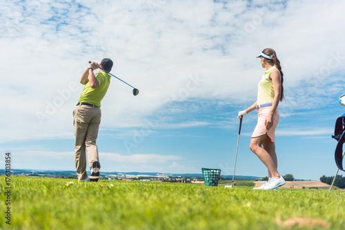 Plakat Pełna długość młoda kobieta uśmiecha się podczas uprawiania prawidłowego ruchu do uderzania podczas klasy golfa z wykwalifikowanym profesjonalnym graczem na zewnątrz