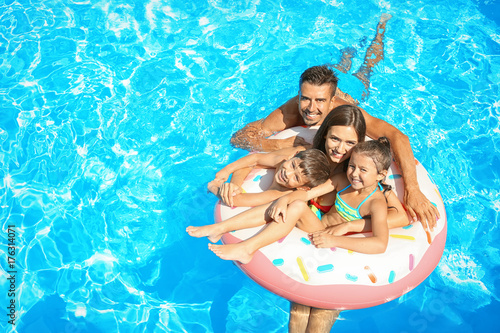Fotografie, Obraz  Happy family with inflatable ring relaxing in swimming pool