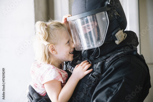 Fotografie, Obraz special policeman holding a little girl in his arms