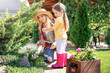 Cute little girl with mother taking care of plants in garden on sunny day
