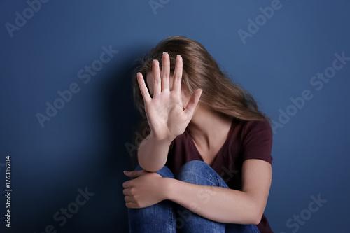 Fényképezés  Battered sad woman sitting alone near blue wall