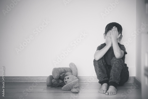 Fototapeta Little sad boy sitting on floor at home obraz na płótnie