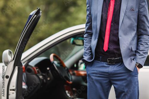 Zdjęcie XXL Pomyślny biznesmen w ciemnym garniturze z czerwonym krawatem przeciw tłu samochód. Stylowy mężczyzna. Modny zegarek na rękę. Ręka w kieszeni