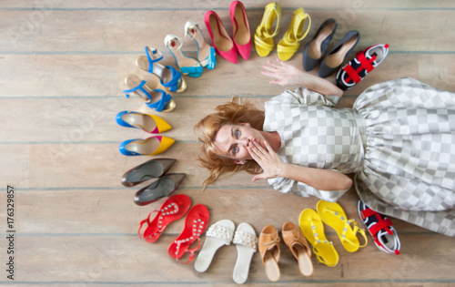 Fotografía  Woman choosing shoes. Colored shoes are exposed in a circle.