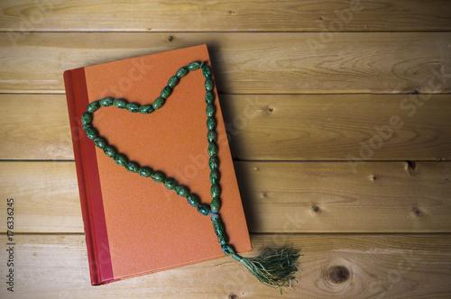 Zdjęcie XXL Widok z góry książka w twardej oprawie z tasbih lub pieczywem. Koncepcja książki duchowej świętości. Selektywna ostrość.