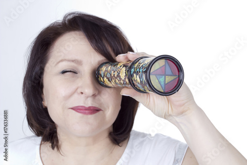 Fotografie, Obraz  Adult woman looking into a kaleidoscope
