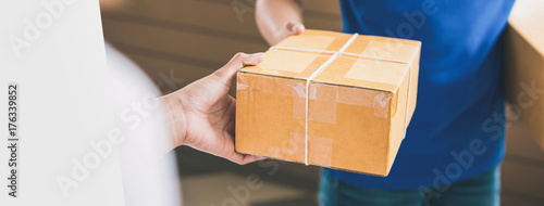 Fotografie, Obraz  Delivery man handing a parcel over to a female customer