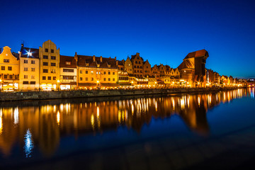 Gdansk old town and famous crane, Polish Zuraw. View from Motlawa river, Poland at romantic sunset, night.