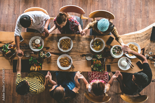 Group of friend pray before having nice food and drinks, enjoying the party and communication, Top view of Family gathering together at home for eating dinner Fototapet