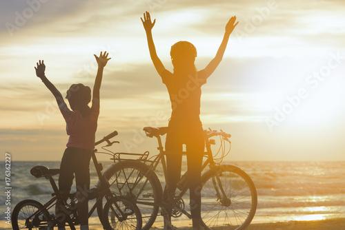 Plakat Sylwetki rowerzysty rodziny na plaży w piękny zachód słońca.