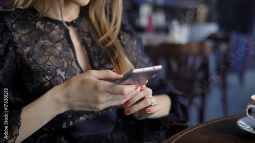 Fototapety, obrazy: young cute woman using phone ,sitting at a cafe holding a smartphone, answering texts. Beautiful business woman in a restaurant during a lunch break, browsing messages online.