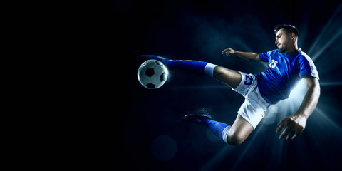 Fototapeta Soccer player performs an action play on a dark background. Player wears unbranded sport uniform.