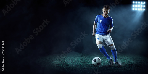 Fotobehang Volle maan Soccer player performs an action play on a dark background. Player wears unbranded sport uniform.