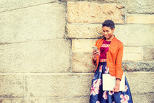 Unhappy Young African American Woman Thinking Outside In New York, Wearing Orange Red Jacket, Flower Patterned Skirt, Black Boot Shoes, Holding Laptop Computer, Standing By Stone Wall On Campus, Sad.