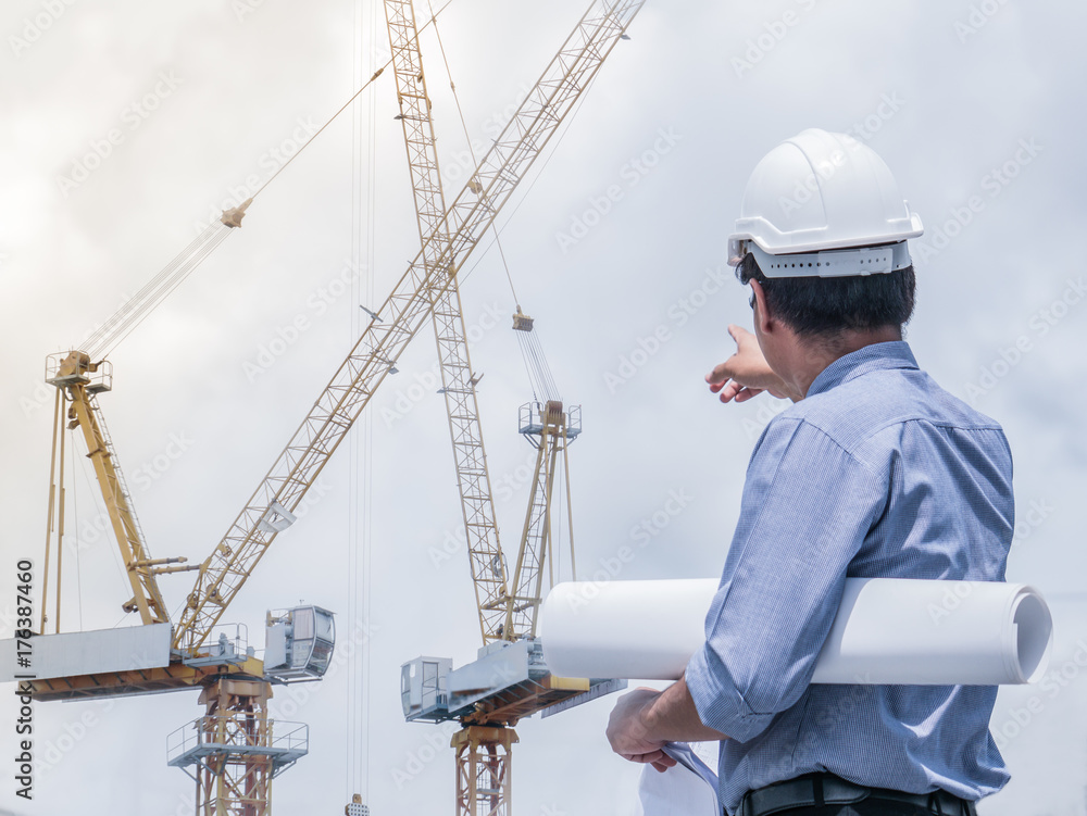 Fototapeta The construction project chief engineer is observing the tower crane operation at the construction site. Double exposure image