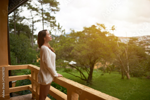 Beautiful Asian woman breathing fresh air on villa balcony in morning Poster
