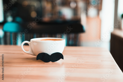 Photo  White mug of coffee with moustache on wooden table at coffee shop