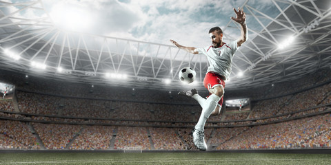 Fototapeta Soccer player performs an action play and beats the ball on a professional stadium. Player wears unbranded sport uniform.