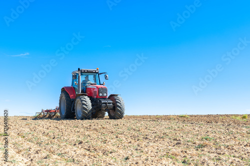 Fotografia  agricultural tractor in the foreground with blue sky background.