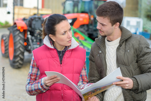 Foto  saleswoman convincing young famrer to buy new agricultural machinery