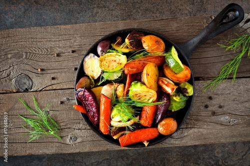Staande foto Groenten Cast iron skillet of roasted autumn vegetables against a rustic dark background