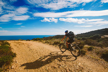 A Young Guy Riding A Mountain Bike On A Bicycle Route In Spain On Road Against The Background Of The Mediterranean Sea. Dressed In A Helmet, A Dark One And A Black Backpack