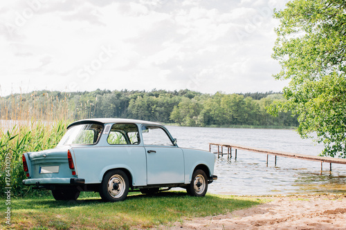 Blue GDR Vintage Car Parked Near Lake on Sunny Summer Day Wallpaper Mural